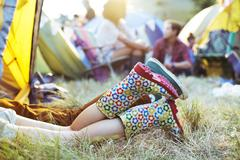 Couple's legs sticking out of tent at music festival - stock photo