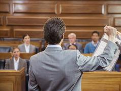 Lawyer showing documents to jury in court - stock photo