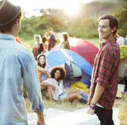 Men carrying cooler outside tents at music festival Stock Photos