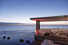 Cabana and infinity pool overlooking ocean - stock photo