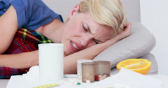 Sick woman blowing his nose while she is lying on bed Stock Footage
