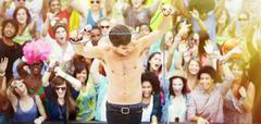 Performer dancing on stage with fans cheering in background at music festival - stock photo