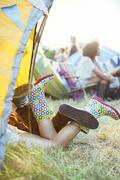 Couple's legs sticking out of tent at music festival Stock Photos