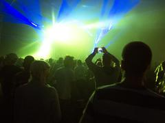 Silhouette of crowd facing illuminated stage at music festival - stock photo
