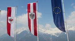 Tyrol, Austrian, EU flags waving, grand snowy Alps on background Stock Footage
