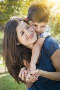 Attractive Young Mixed Race Mother and Son Hug Outdoors in the Park. - stock photo