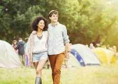 Couple walking outside tents at music festival Stock Photos