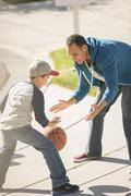 Stock Photo of Father and son playing basketball in sunny driveway