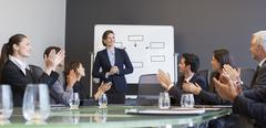 Business people applauding colleague in meeting - stock photo