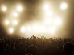 Silhouetted crowd watching illuminated stage at music festival - stock photo