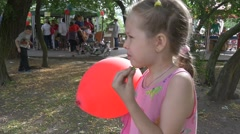 Girl in Pink Dress With Fair Braid Is Standing, Eating And Keeping Red Ballon in Stock Footage