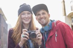 Couple taking photographs with camera in city Stock Photos