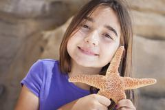 Young Pretty Girl Playing with Starfish. Stock Photos