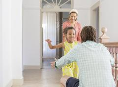 Father and daughter embracing in living space - stock photo