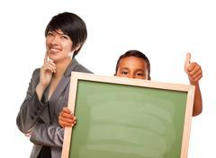 Hispanic Boy Holding Chalk Board and Female Teacher Behind - stock photo