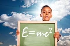 Proud Hispanic Boy Holding Chalkboard with Theory of Relativity - stock photo
