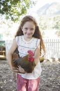 Girl holding chicken at petting zoo Stock Photos