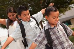 Cute Brothers and Sister with Backpacks Having Fun Walking to School. - stock photo