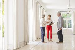 Older couple talking with woman in living space Stock Photos