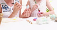 Mother and daughter painting easter eggs Stock Footage