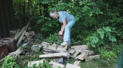 Country Senior Woman Doing Chore of Cutting Fire Wood with Chainsaw Stock Footage
