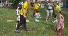 Children Play A Game Throw Stones In Iron Boxes Stock Footage
