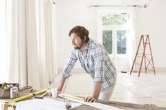 Man overlooking construction table in living space Stock Photos
