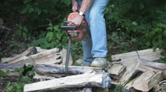 Country Senior Woman Doing Chore of Cutting Fire Wood with Chainsaw - stock footage