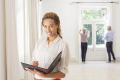 Woman holding binder in living space - stock photo
