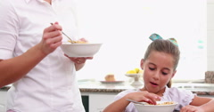 Mother and her daughter eating cereals together Stock Footage