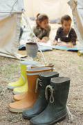 Rainboots lined up outside tent at campsite - stock photo