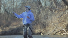 Pan across a young fly fisherman casting his line Stock Footage