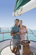 Couple steering sailboat together Stock Photos