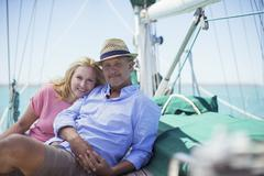 Couple sitting on deck of sailboat Stock Photos