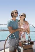 Couple steering boat together - stock photo