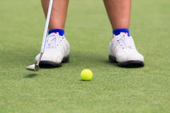 Woman golf player putting on the green Stock Photos
