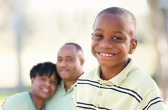 Handsome African American Boy with Proud Parents Standing By in the Park. Stock Photos