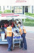 Paramedics wheeling patient out of ambulance - stock photo