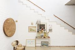 Side table and wall hangings by staircase Stock Photos