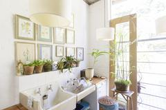 Wall hangings and lights over rustic kitchen sink - stock photo