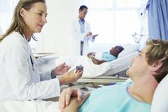 Doctor explaining medication to patient in hospital - stock photo