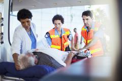 Paramedics and nurse examining patient in ambulance - stock photo
