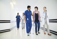 Doctor and nurse walking patient down hospital hallway Kuvituskuvat
