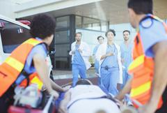 Doctors and nurses rushing to patient on ambulance stretcher Stock Photos