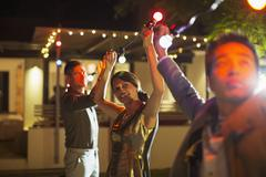Friends stringing lights at outdoor party Stock Photos