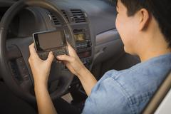 Mixed Race Woman with Smart Phone Texting and Driving. - stock photo
