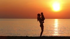 Silhouette of mother playing with kid on beach at sunrise Stock Footage