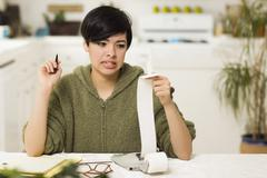 Mixed Race Young Female Agonizing Over Financial Calculations in Her Kitchen. Stock Photos