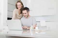 Couple using laptop at breakfast table Stock Photos