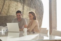 Couple using laptop at breakfast - stock photo